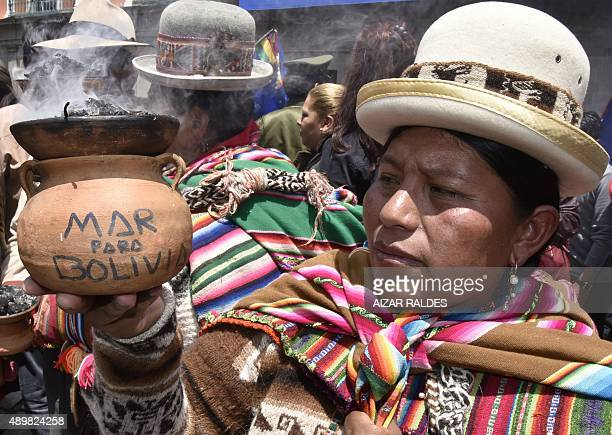 An Aymara indigenous woman shows a ceremony burner reading 'Sea To Bolivia' during a meeting with Bolivian President Evo Morales to celebrate the...
