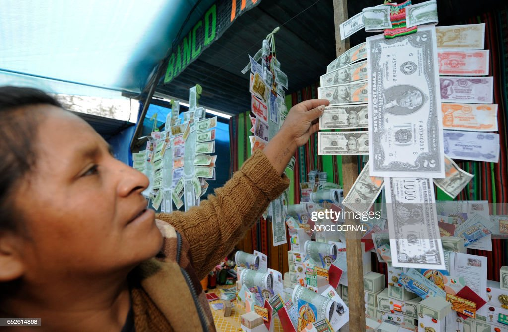 An Aymara native woman sells notes during the Alasitas --'buy from me' in native language-- festival to honor the Ekeko, the Aymara God of Abundance, on January 24, 2012 in La Paz. During the yearly festivity, Bolivians buy miniatures of material things they want for the upcoming year and offer them to Ekeko, pinning them onto his poncho. AFP PHOTO/Jorge Bernal /