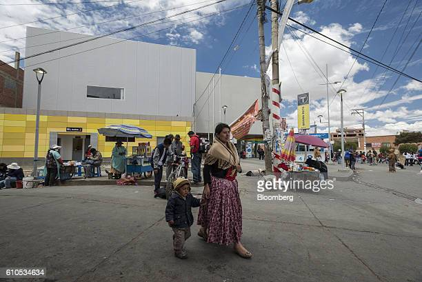 An Aymara woman dressed in traditional clothes walks outside the yellow line Mi Teleferico cable car station in El Alto, Bolivia, on Sunday, Sept. 4,...