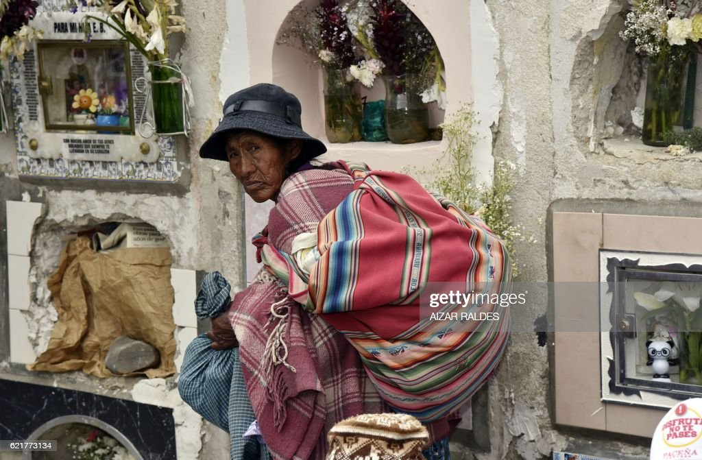 An Aymara woman wals amid tombs at the Central Cemetery of La Paz, on November 8, 2016 during the celebration of the festivity of the 'natitas' (snub-nosed). The natitas are meant to protect their owners, who keep them at home all year long and bring them to the cemetery chapels every 8 of November to perform rituals which end up in a traditional party. /