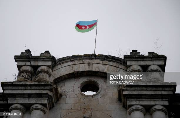 An Azerbaijani flag waves on a building in Fuzuli on November 18, 2020. - The territory is due to be returned to Baku as stipulated in a...