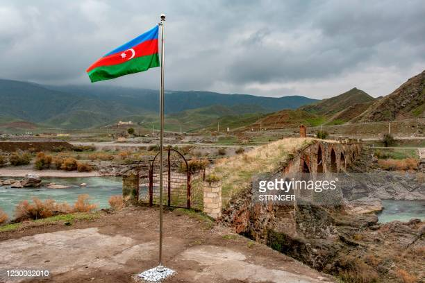 An Azerbaijani national flag flies next to the mediaeval Khudaferin bridge in Jebrayil district at the country's border with Iran - the territories...