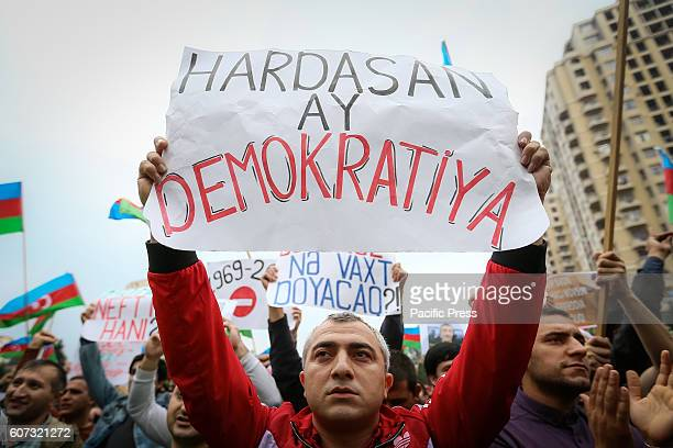 An Azerbaijani opposition supporter holds a placard reading 'Where is the democracy' as he takes part in a demonstration The protesters are...