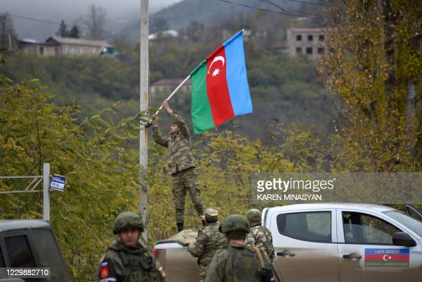 An Azerbaijani soldier fixes a national flag on a lamp post in the town of Lachin on December 1, 2020. - Azerbaijani soldiers and military trucks on...
