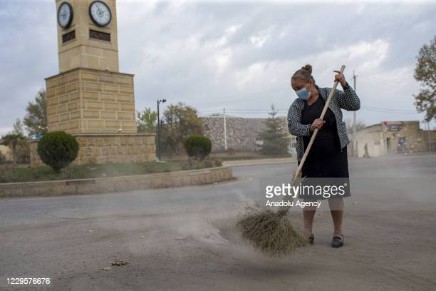 An Azerbaijani woman sweeps a broom on the street of Terter after the deal reached to halt fighting over the Nagorno-Karabakh region as the defeat of...
