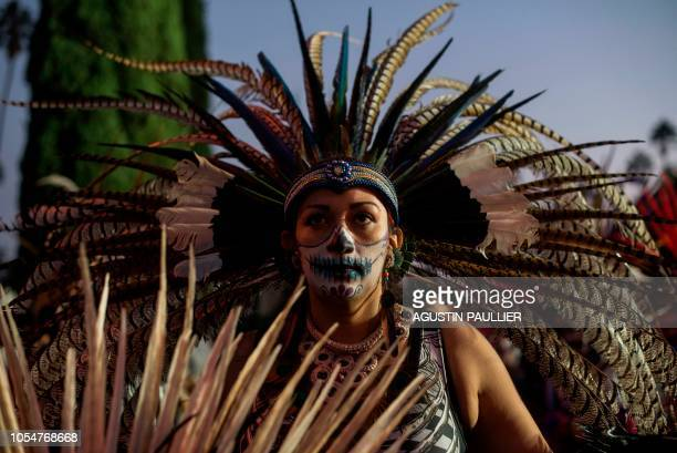 TOPSHOT An Aztec ritual dancer performs at Hollywood Forever Cemetery's 19th annual Dia De Los Muertos celebration in Hollywood California on October...