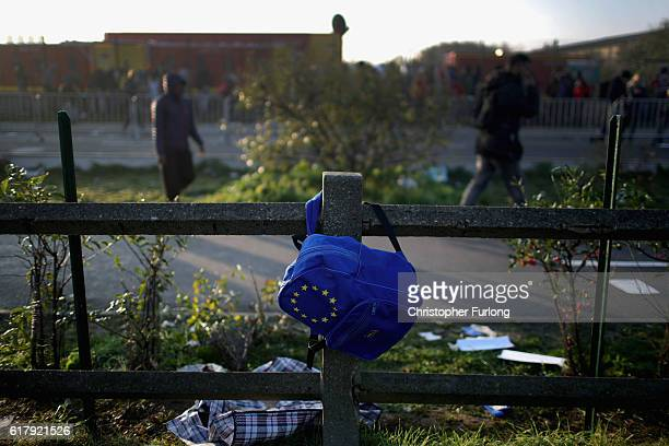 An bag with the EU flag is dscarded as migrants queue to board buses and leave the notorious 'Jungle' camp before authorities demolish the site on...