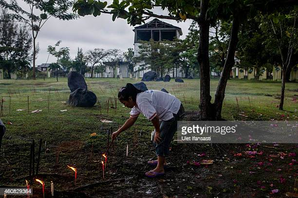 An Buddhist worshiper lights incense sticks as they pray for victims to commemorate the ten anniversary of tsunami at mass grave on December 25 2014...