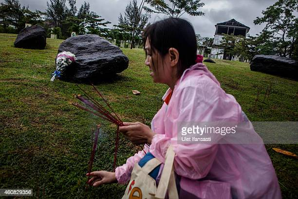 An Buddhist worshiper put incense sticks as they pray for victims to commemorate the ten anniversary of tsunami at mass grave on December 25 2014 in...
