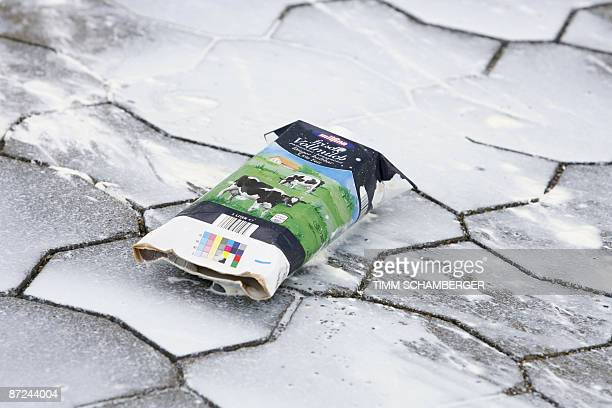 An burst carton of milk lies on the pavement during a dairy farmers' demonstration in front of German the nofrills supermarket Aldi against falling...