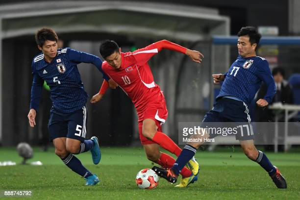 An Byong Jun of North Korea competes for the ball against Shintaro Kurumaya and Yasuyuki Konno of Japan during the EAFF E1 Men's Football...