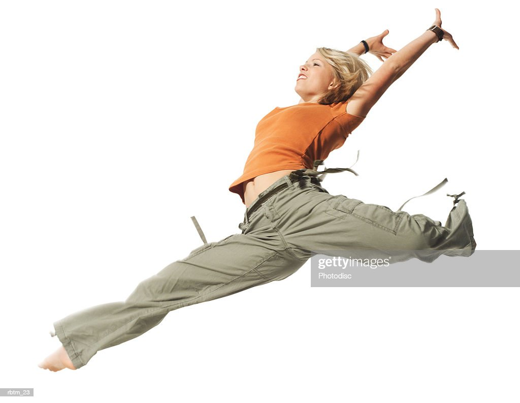 an caucasian blonde female teen in green pants and an orange shirt jumps through the air : Foto de stock