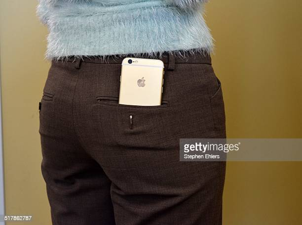 An champagne gold colored iPhone 6 in a woman's back pocket
