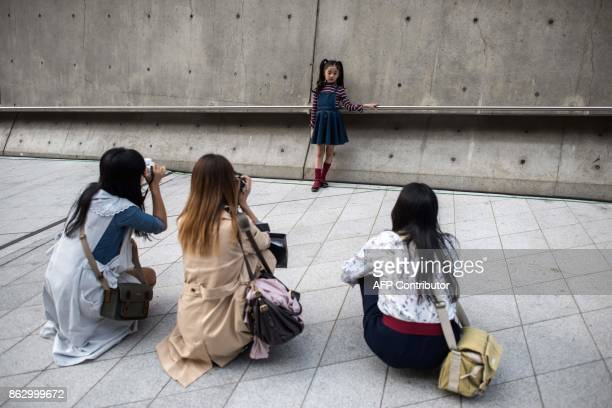 TOPSHOT An child poses for photographers during Seoul Fashion Week at Dongdaemun Design Plaza in Seoul on October 19 2017 For Seoul's flamboyant...