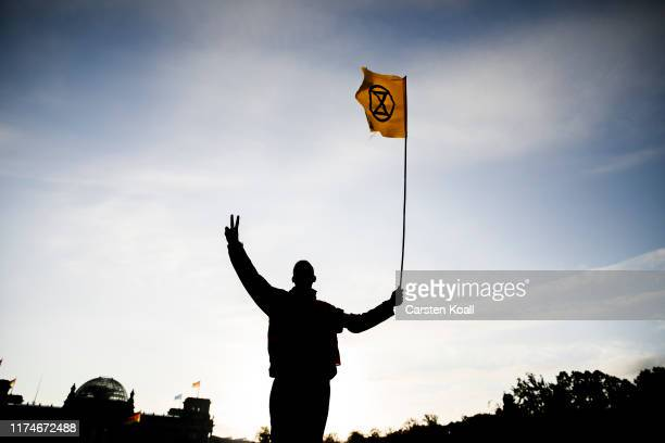 An climate activist waves a flag between the Reichstagsbuildung and a camp they have pitched next to the Chancellery on October 9, 2019 in Berlin,...