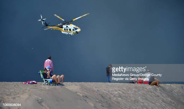 An LA County fire helicopter comes in for a landing over evacuees at the Zuma Beach helipad where it will be refilled with water before attacking the...