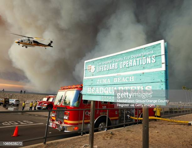 An LA County fire helicopter takes off from the Zuma Beach helipad where it was filled with water before attacking the Woolsey Fire in Malibu on...