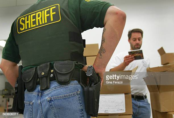 An LA County Sherifff officer stands guard while Chuck Hausman of the anit–piracy unit of the RIAA checks suspect CD's during a raid at Media Tek...