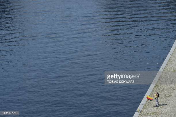 "An demonstrator holds a German flag along the river Spree during the ""demonstration for the future of Germany"" called by the far-right AfD at the..."