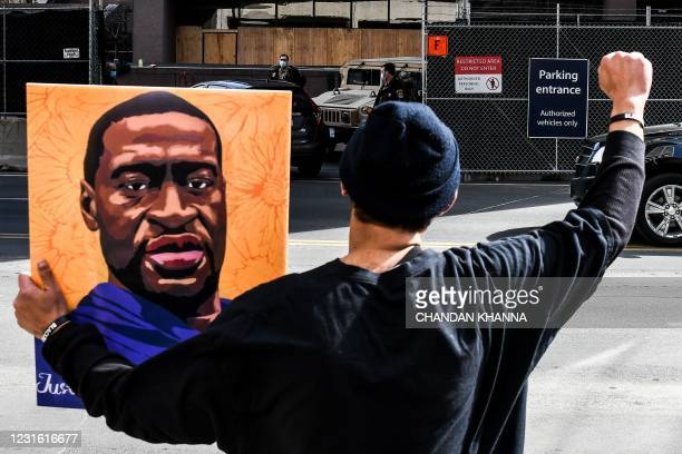 An demonstrator holds a portrait of George Floyd outside the Hennepin County Government Center on March 9, 2021 in Minneapolis, Minnesota. - Jury...