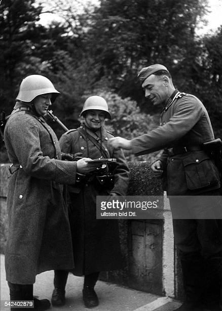 An der schweizerischdeutschen Grenzedeutscher Soldat nimmt eine Zigarredie ihm ein Schweizer Füsilier anbietet November 1939