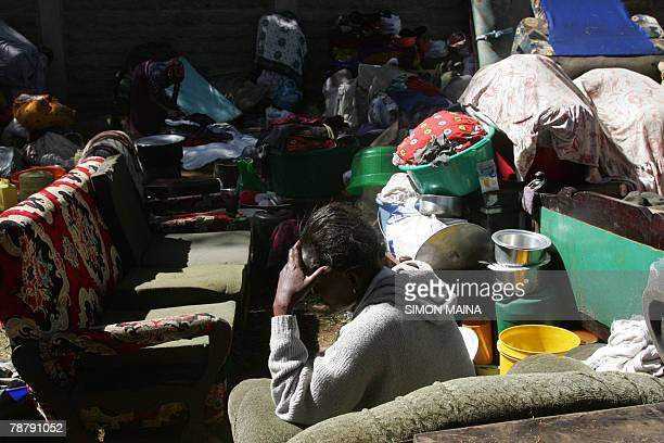 An displaced woman sits next to her belongings at the Kenyan airforce military base outside Mathare in Nairobi 06 January 2008 A devastating health...