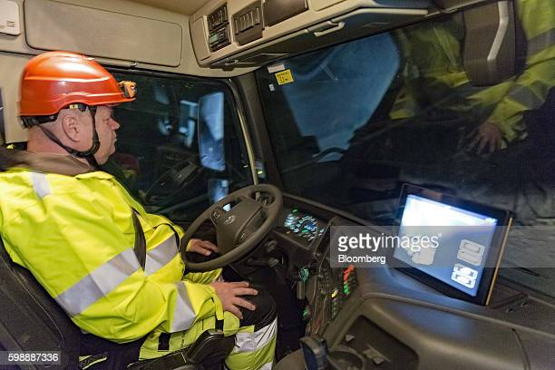 An driver rests his hands away from the steering wheel of a Volvo Autonomous FMX selfdriving truck manufactured by Volvo Group as it drives through...