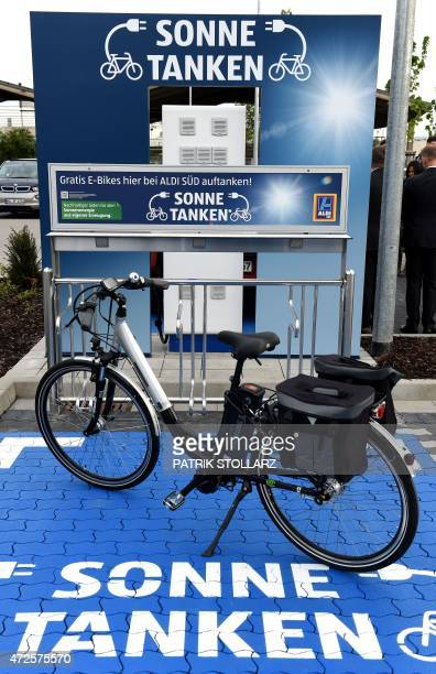 An e bike stands in front of a new charging station for electro cars on the carpark in front of an Aldi South supermarket discount store on May 8...