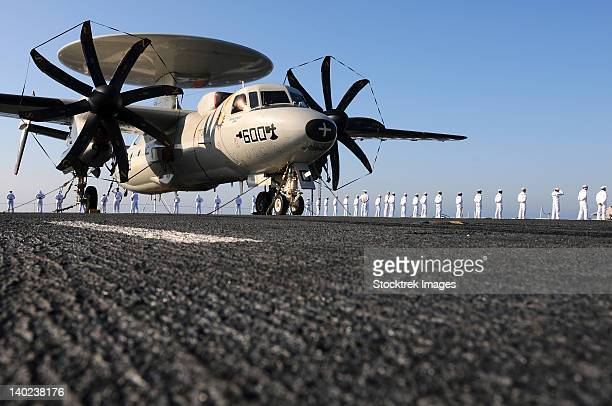 An E-2C Hawkeye sits on the flight deck of USS Abraham Lincoln while sailors man the rails.