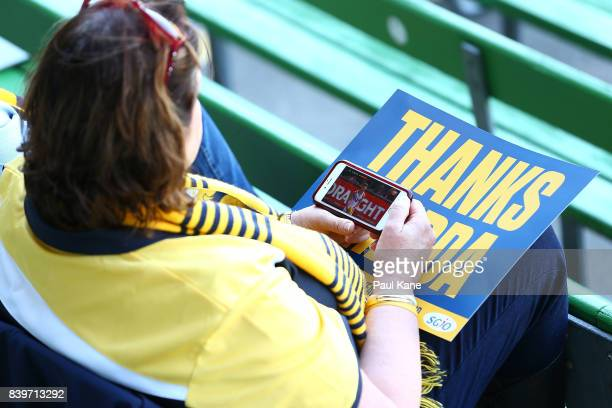 An Eagles supporter watches the Essendon v Fremantle game on her smart phone before the round 23 AFL match between the West Coast Eagles and the...