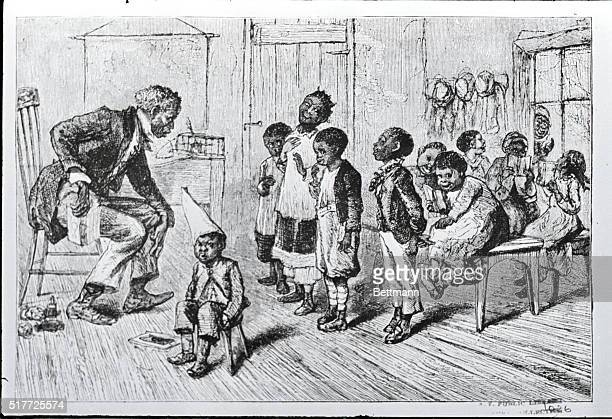An early American African American Village School Photo shows teacher helping students in a classroom ca1880