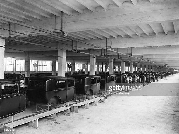 An early assembly line for car manufacturing