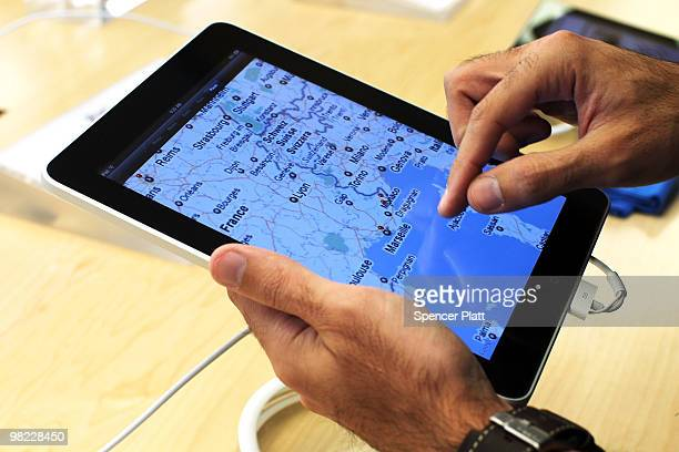 An early customer at the Apple store on Fifth Avenue tries Apple Inc's new iPad on April 3 2010 in New York City Hundreds lined up in front of the...