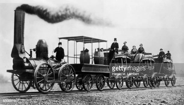 An early English steam locomotive hauling a tender and three carriages adapted from horsedrawn coaches