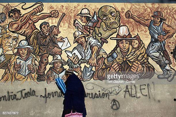 An early evening scene in Potosi Bolivia as a women walks past a mural depicting the history of the town Potosi Bolivia 12th May 2010 Photo Tim...
