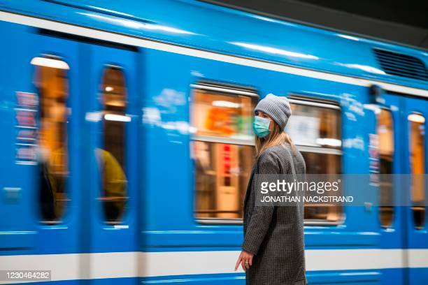 An early morning commuter on Stockholm's metro wears a face mask as a recommendation came into effect on January 7, 2021 from the country's public...