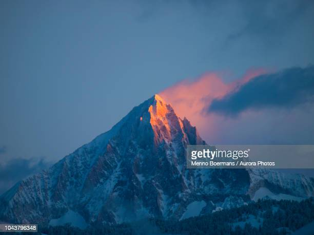an early morning picture of the first sun rays setting the pyramid summit of the bietschhorn mountain on fire. - european alps stock pictures, royalty-free photos & images