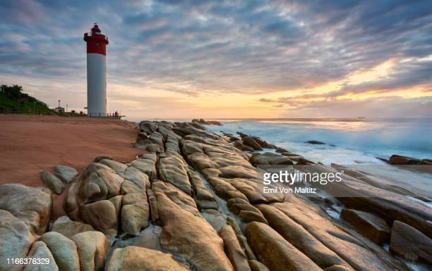 an early morning picturesque stratocumulus sky of the iconic umhlanga rocks lighthouse and waves rolling onto the rocks on the shore. durban, kwazulu-natal natal, south africa - ダーバン ストックフォトと画像