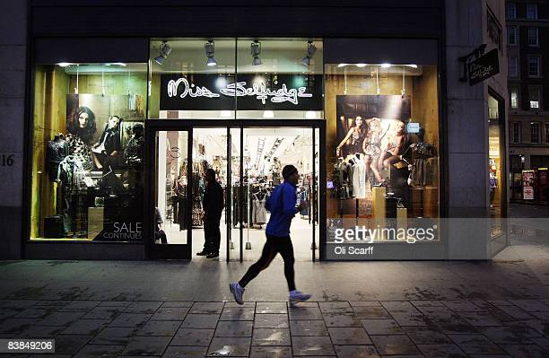 b3f4374adaa04 An early morning runner passes the Miss Selfridge clothing store in Oxford  Street shortly after 7am. Christmas Retail Shopping