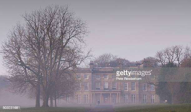 An early morning scene as mist envelops Haigh Hall and it's surroundings with a lone dog walker.