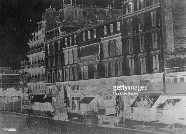 An early negative by Hippolyte Bayard on paper of a facade on a French city street
