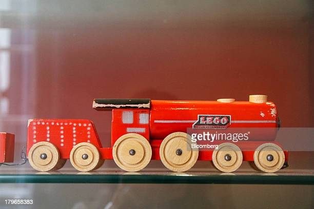 An early wooden toy locomotive manufactured by Lego A/S stands on display in the showroom at the company's headquarters in Billund Denmark on...