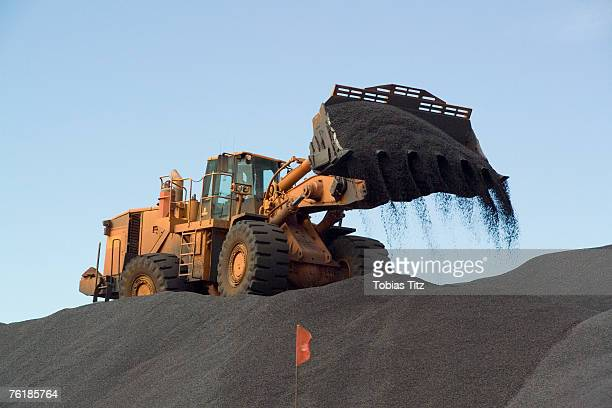an earth mover pouring gravel - dump truck stock pictures, royalty-free photos & images