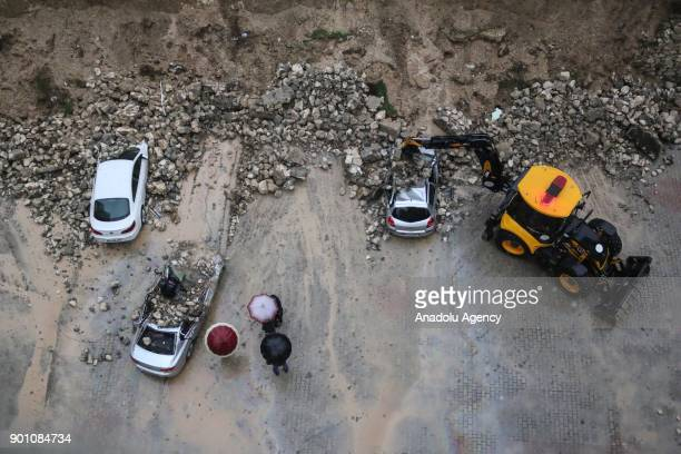 An earth mover removes rubbles over a crashed car following the collapse of a retaining wall due to heavy rain in Adana province of Turkey on January...