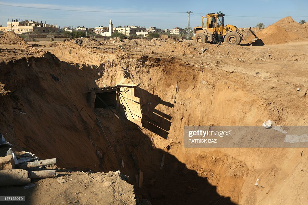 An earth mover repairs a bombed smuggling tunnel linking the Gaza Strip to Egypt (seen in the background) in Rafah on November 29, 2012. Israeli airforce jets bombed most of the smuggling tunnels in the southern Gaza Strip during its war against the Islamist movement Hamas, which rules the coastal Palestinian territory, between 14 to 21 of November 2012.