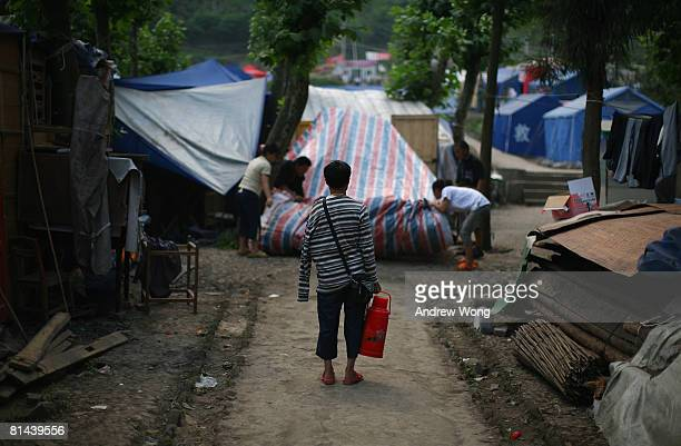 An earthquake survivor carries a kettle as others try to set up a tent at a refugee camp on June 5, 2008 in Shifang, Sichuan province, China. More...