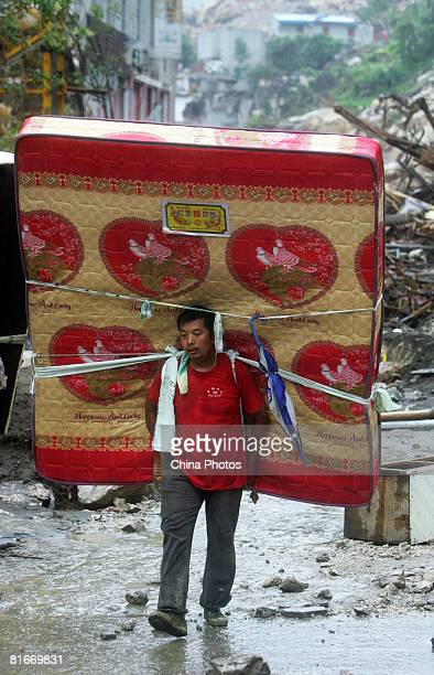 An earthquake survivor carries a mattress on his back on June 22 2008 in Beichuan County of Sichuan Province China The evacuated residents returned...