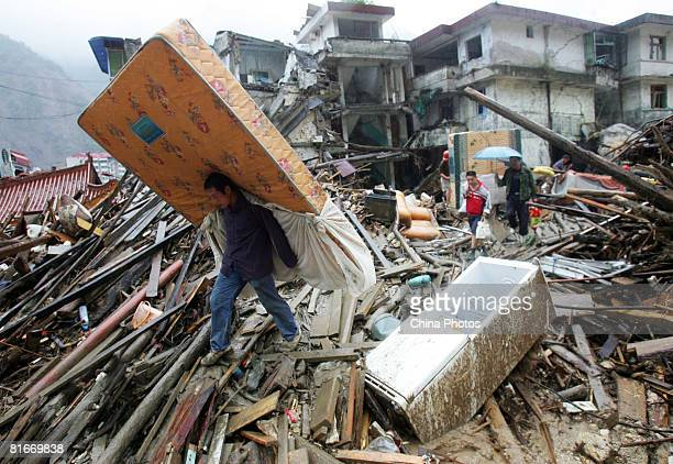 An earthquake survivor carries a mattress recovered from the debris on June 22 2008 in Beichuan County of Sichuan Province China The evacuated...