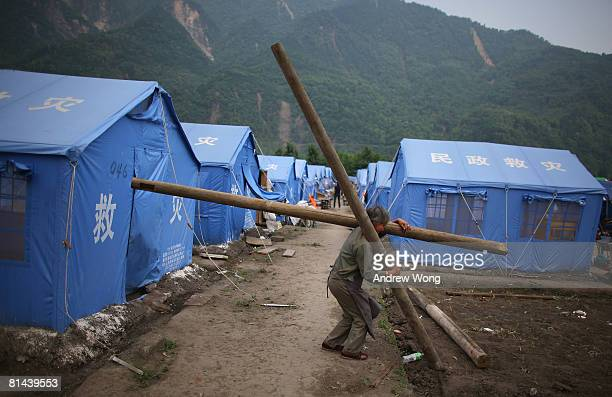 An earthquake survivor carries building materials at a refugee camp on June 5, 2008 in Shifang, Sichuan province, China. More than 69,000 people are...