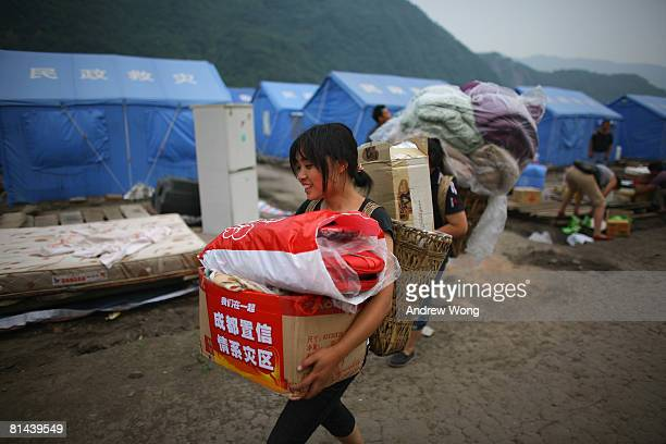 An earthquake survivor carries government relief supplies handed out to her at a refugee camp on June 5, 2008 in Shifang, Sichuan province, China....